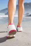 Fit woman walking on the beach. On a sunny day royalty free stock photography