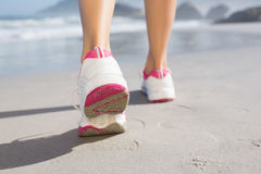 Fit woman walking on the beach. On a sunny day stock image