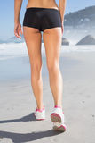 Fit woman walking on the beach. On a sunny day stock photos