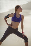 Fit woman warming up on beach Stock Images