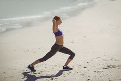 Fit woman warming up on beach Stock Photography