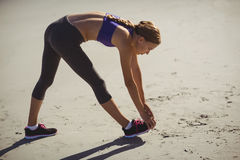 Fit woman warming up on beach Royalty Free Stock Photo