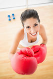 Fit woman wearing red boxing gloves smiling at camera Stock Photos