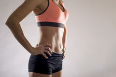 Fit woman wearing shorts and sport top showing slim beautiful stomach and abs. Cropped close up body of fit woman wearing shorts and sport top showing slim royalty free stock images