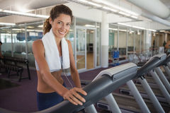 Fit woman wearing towel around shoulders on the treadmill Royalty Free Stock Photography