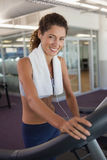 Fit woman wearing towel around shoulders on the treadmill Stock Photos