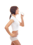 A fit woman in white sporty clothes drinking water Royalty Free Stock Images