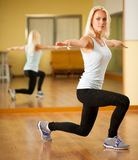 Fit woman work out in gym making lunge step Stock Image