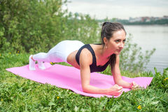 Fit woman working on back and abdominal muscles, doing plank exercise abs core workout in nature. Fit woman working on back and abdominal muscles, doing plank stock images