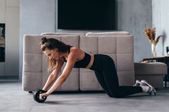 Fit woman working out with ab exercise wheel at home.