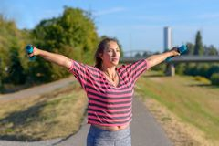 Fit woman working out in a city park. Lifting dumbbell weights in early morning sunshine in a health and fitness concept stock photos