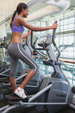 Fit woman working out on the cross trainer Stock Images