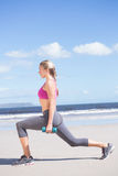 Fit woman working out with dumbbells on the beach lunging Stock Photo