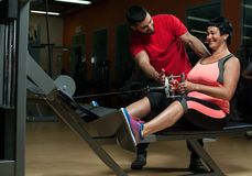 Fit woman working out in gym with personal coach. Fit brunette women working out in gym with assistance of personal coach. Young male trainer with female client Royalty Free Stock Image