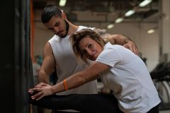 Fit woman working out in gym with personal coach. Fit blonde women working out in gym with assistance of personal coach. Young male trainer with female client Royalty Free Stock Photos