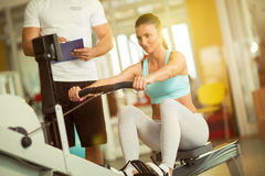 Fit woman working out on row machine in gym Stock Image