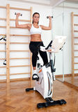 Fit woman working out on stationary bicycle Royalty Free Stock Photo
