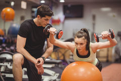Fit woman working out with trainer. Fit women working out with trainer at the gym Royalty Free Stock Photography
