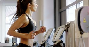 Fit woman in workout clothes running on treadmill machine in fitness gym stock video