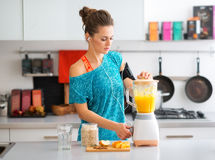 Fit woman in workout gear in kitchen making a smoothie Royalty Free Stock Images