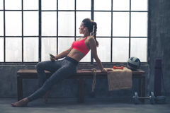 Fit woman in workout gear sitting in profile in loft gym Royalty Free Stock Photo