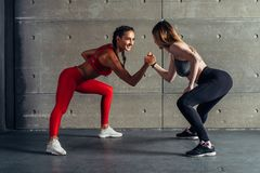 Fit woman wrestle on hands with a female opponent looking in her eyes. Fit women wrestle on hands with a female opponent looking in her eyes stock photos
