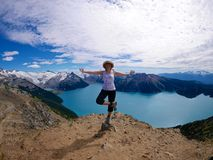 Fit Woman in Yoga Pose at Alpine Lake Surrounded with Snow Capped Mountains. Royalty Free Stock Photo