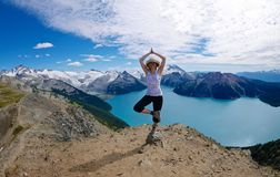 Fit Woman in Yoga Pose at Alpine Lake Surrounded with Snow Capped Mountains. Royalty Free Stock Photos