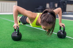 Fit woman young doing push ups exercise with dumbbells in the gym Stock Photos