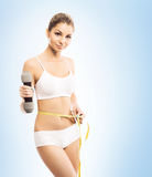 Fit womanl with a dumbbell and a measuring tape Stock Image