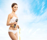 Fit womanl with a dumbbell and a measuring tape Royalty Free Stock Photography