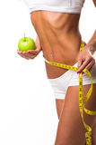 Fit women  body with apple and measuring tape Stock Photos