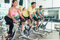 Fit women burning calories during indoor cycling class in a fitness club. Rear low-angle view of two fit women with an active lifestyle burning calories during royalty free stock photo
