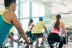 Fit women burning calories during indoor cycling class Royalty Free Stock Photography