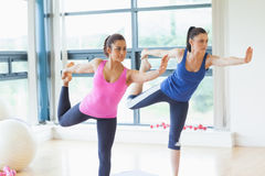 Fit women doing the balancing yoga pose in fitness studio Royalty Free Stock Photo