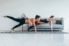 Fit women doing one hand one leg plank exercise workout at home. Fit women doing one hand one leg plank exercise workout at home stock image
