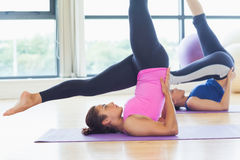 Fit women doing the shoulder stand posture in fitness studio Royalty Free Stock Photo