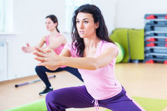 Fit women doing side lunges, exercises for legs, hips and buttocks. Stock Image