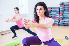 Fit women doing side lunges, exercises for legs, hips and buttocks. Fit women doing side lunges, exercises for legs, hips and buttocks Royalty Free Stock Photography