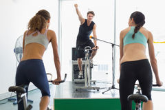 Fit women doing a spin class with enthusiatic instructor Stock Photo