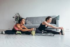 Fit women doing stretching while sitting on the floor at home stock image