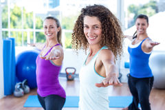 Fit women doing warrior II pose in fitness studio Royalty Free Stock Images