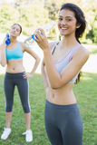 Fit women drinking water in park Royalty Free Stock Photos