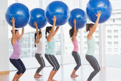 Fit women holding blue fitness balls in exercise room Stock Photography