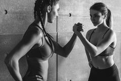 Fit women holding hands with a female opponent looking in her eyes. Fit women holding hands with a female opponent looking in her eyes royalty free stock photography