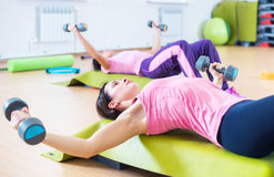 Fit women lifting dumbbell while lying on step platforms. Royalty Free Stock Photo