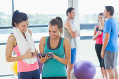 Fit women looking at digital table with friends chatting in background Stock Image