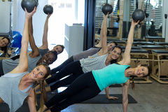 Fit women performing stretching exercise with fitness ball in gym Stock Photography