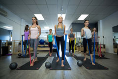 Fit women performing stretching exercise with resistance band Royalty Free Stock Photos
