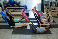 Fit women performing stretching exercise with resistance band in gym Stock Photos